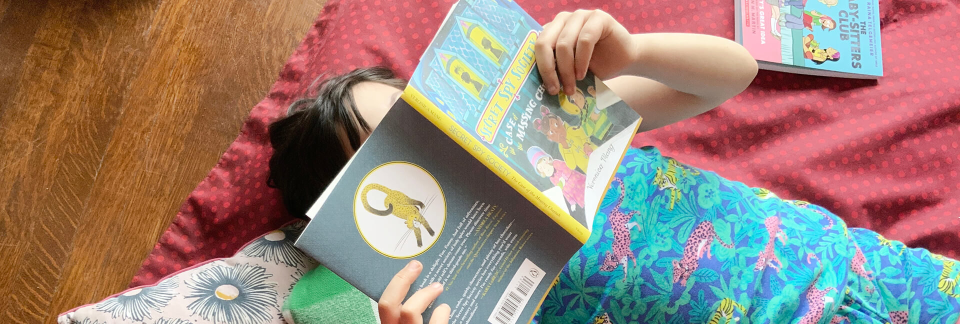 Girl holding book over her face wearing a Hatley sleepwear set.