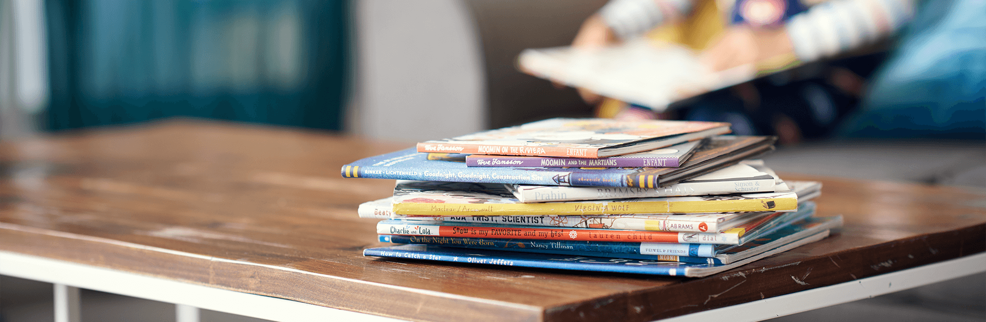 A stack of books on a table and a boy reading a book on a couch in the distance.