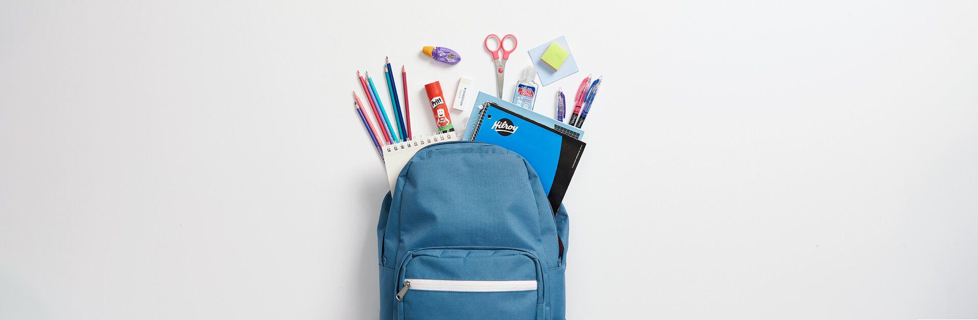 Blue back pack with and assortment of school supplies.