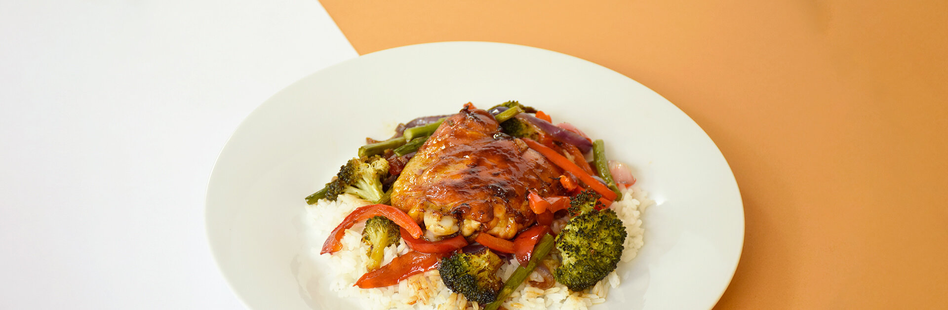 Hoisin ginger chicken, vegetables and rice on a plate.