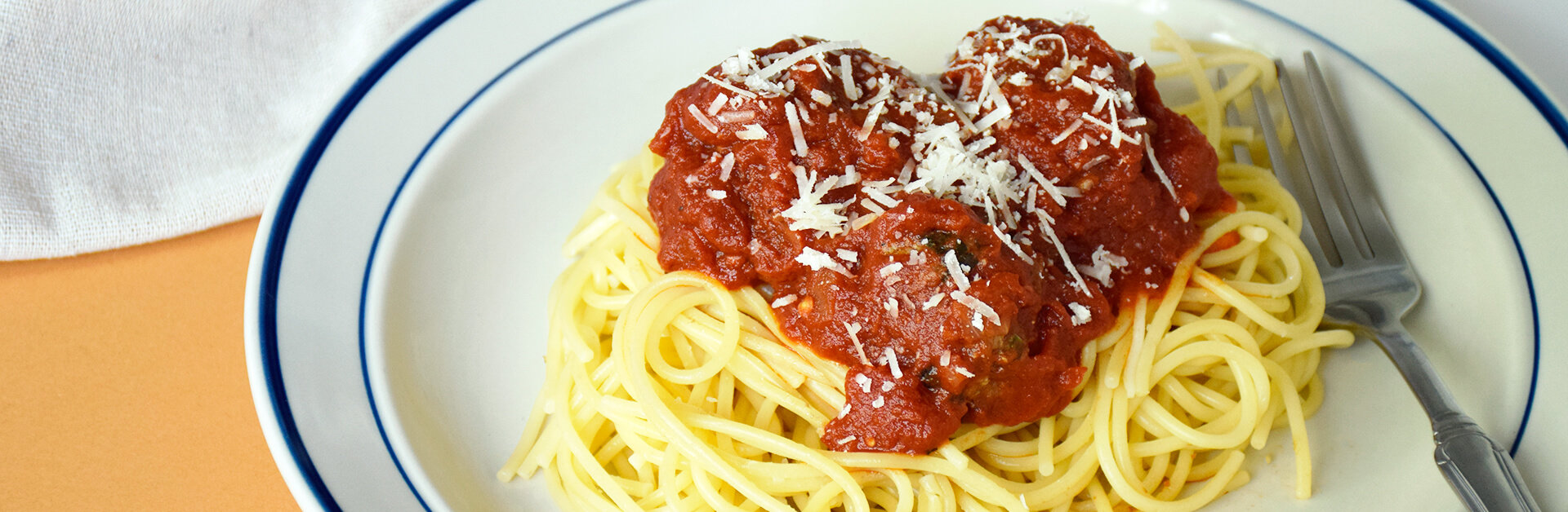 Spaghetti and meatballs on a white plate with blue edges.