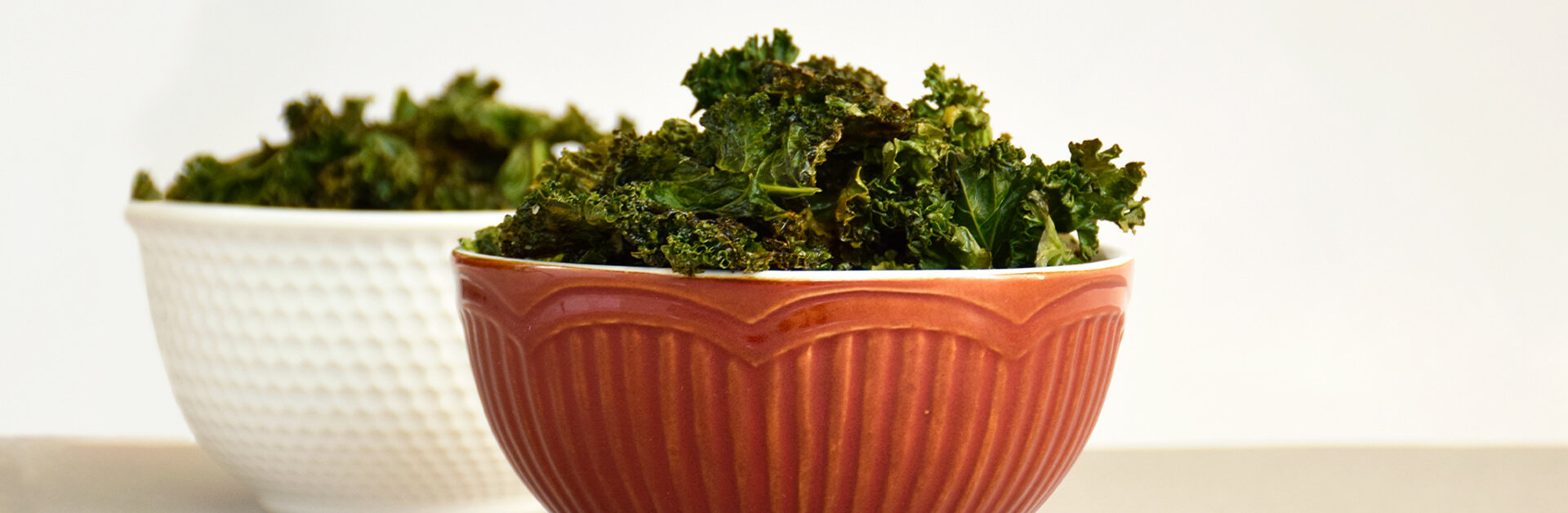Two bowls of baked kale chips.
